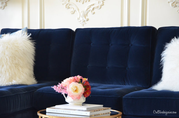 Navy tufted sofa with pillows