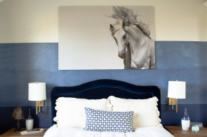 Navy ombre wall and brass wall sconces and a large horse picture